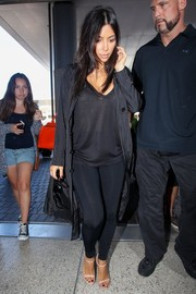 Kim Kardashian kept it comfy in a black Splendid V-neck tee and a pair of leggings during a flight from LAX.