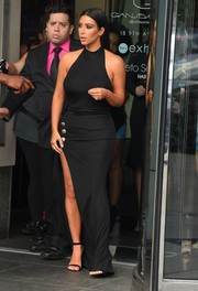 Kim Kardashian wowed on the streets of NYC in a slinky black halter dress with a thigh-high slit.