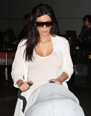 Kim Kardashian looked cool and sporty in her designer shield sunglasses as she arrived at LAX.
