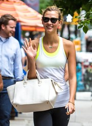 Karlie Kloss completed her strolling ensemble with a pair of Ray-Ban wayfarers.