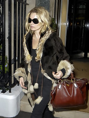 Kate Moss accented her fur-trimmed coat with messy hair and a rich cognac leather purse.