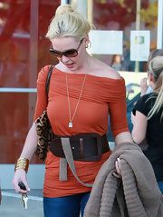 Katherine Heigl wears an oversized dark leather belt with her off the shoulder orange knit top.
