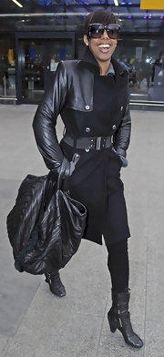 Kelly Rowland was all smiles as she arrived at Heathrow Airport carrying a black oversized leather tote with tonal striping.