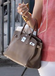 "Kelly Rutherfod strolled down the street looking ready for spring in her coral colored tank. She went neutral with a tan ""Birkin"" bag to top off her look."