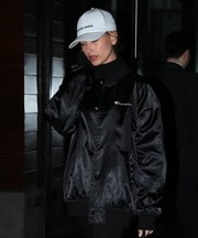 Hailey Baldwin looked sporty in a white Balenciaga baseball cap teamed with a black bomber jacket while enjoying a night out.