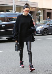 Kendall Jenner injected a sporty touch with a pair of red and black high-top sneakers by Nike.