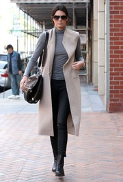 Kendall Jenner topped off her cool getup with a sleeveless nude coat by Acne Studios.