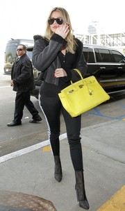 Khloe Kardashian teamed a cropped leather jacket by Yeezy with a pair of Adidas pants for her airport look.
