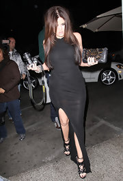 Khloe Kardashian dined out intricate black strappy sandals, which added a sultry finish to her floor length jersey gown.