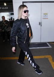 Khloe Kardashian teamed two-tone track pants by Off-White with a black bomber jacket for a flight.