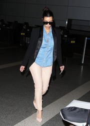 Kim Kardashian landed at LAX looking cool in a Balmain denim shirt under a black tux jacket.