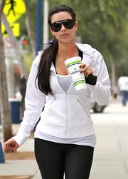 Kim sipped a smoothie while sporting blacked-out shield sunglasses.
