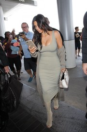 Kim Kardashian played up her amazing curves in a taupe tank dress by Mark Wong Nark while catching a flight at LAX.