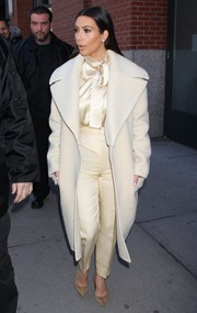 Kim Kardashian turned heads on the streets of NYC with her stylish monotone outfit, consisting of high-waist pants, a tie-neck silk blouse, and a wool coat.