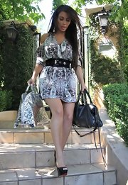 Kim Kardashian showed off her printed day dress, which she paired with an equally stunning monogrammed tote bag.