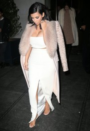 Kim Kardashian matched her miniscule top with a long white front-slit skirt, also by Calvin Klein.