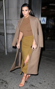 Kim Kardashian styled her outfit with sexy orange ankle-wrap sandals.