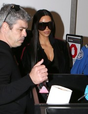Kim Kardashian caught a flight out of LAX wearing a pair of Rick Owens shield sunglasses that covered half her face!