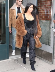 Kim Kardashian contrasted her skimpy top with baggy black drawstring pants.