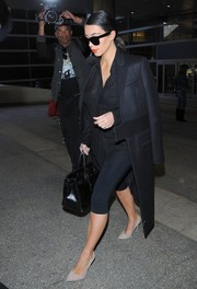 Kim Kardashian landed at LAX looking sleek in a black wool coat.