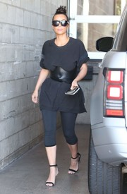 Kim Kardashian stopped by Milk Studios rocking an oversized black tee, which she cinched in with a corset belt.