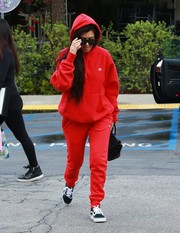 Kourtney Kardashian amped up the sporty feel with a pair of red Champion + UO jogging pants.