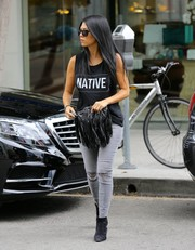 For her footwear, Kourtney Kardashian chose black suede ankle boots by Saint Laurent.