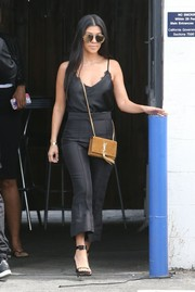 Kourtney Kardashian styled her all-black outfit with a tasseled tan shoulder bag by Saint Laurent.