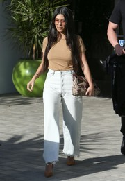 Kourtney Kardashian topped off her jeans with a plain beige tee.