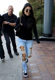 Kourtney Kardashian completed her casual look with a pair of black-and-white canvas sneakers by Vans.
