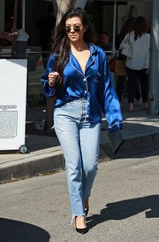 Kourtney Kardashian stayed comfy in a blue silk pajama top while running errands in LA.
