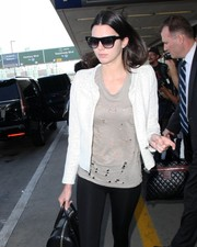 Kendall Jenner arrived on a flight at LAX hiding behind a pair of modern square shades.