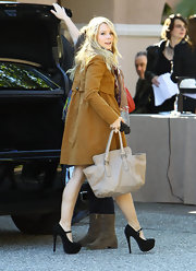Kristen Bell paired her rich mustard coat with a lovely off white leather tote.