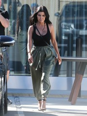 Kourtney Kardashian teamed her tank top with a pair of army-green harem pants.
