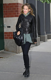 Leelee rocks a pair of black combat boots with matching skinny jeans. A chic leather jacket and sage scarf complete the look.