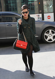 Lily Allen added a pop of color to her Chanel show attire with a red quilted flap bag with multicolored chains.