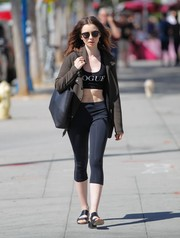 Lily Collins accessorized her look with a black leather shopper bag.