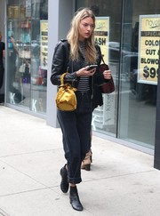 Martha Hunt accessorized with a marigold velvet purse for a bright spot to her look.