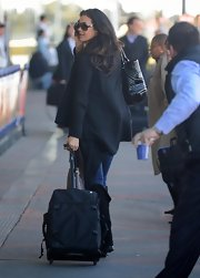 Megan Gale was spotted in the airport with her black rollerboard luggage