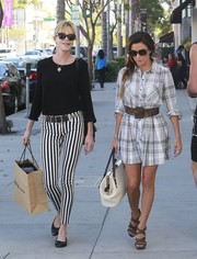 Melanie Griffith paired a black crewneck sweater with striped pants for a day out with BFF Eva Longoria.