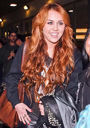 Miley Cyrus turns heads while she shows off her fiery tresses at LAX.