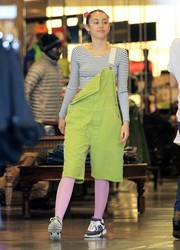 Miley Cyrus wore a pair of knee-length bright green overalls while out shopping. The singer paired the offbeat overalls with a striped shirt, pink tights, and sneakers.