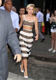 Miley showed off her toned tummy with this black and white, mesh cropped top and matching skirt.