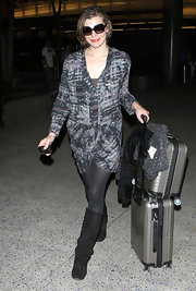 Milla looks chic at the airport in an abstract print dress with tights and boots.