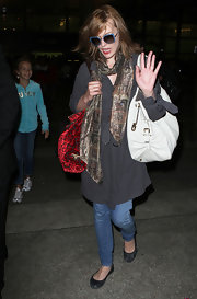 Milla paired her casual airport outfit with a cool leather tote bag.