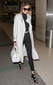Miranda Kerr turned LAX into her own personal catwalk when she caught a flight looking ultra-chic in black leggings, a crop-top, and a white trenchcoat.