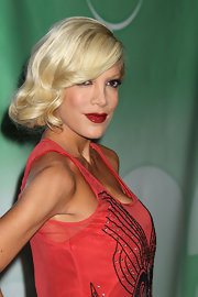 TV reality star Tori Spelling, shows off a classy old hollywood glamour hair style. Here red lipstick and curled mane are reminiscent of a 20's flapper.