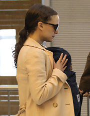 Natalie Portman heads through the airport wearing her hair in a casual ponytail with bobby-pinned bangs.