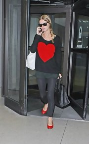 Nicky Hilton accessorized her whimsical sweater with bright red flats.