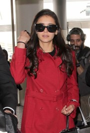 Nina Dobrev looked Parisian-chic wearing oversized butterfly sunnies with a red trenchcoat while catching a flight out of LAX.